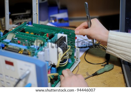 Repairing of microcircute of medical equipment with a help of tweezers - stock photo
