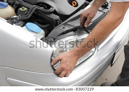 Repairing of modern car, workers hands fixing car light - stock photo