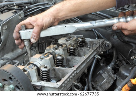 Repairing of modern diesel engine, workers hands and tool - stock photo