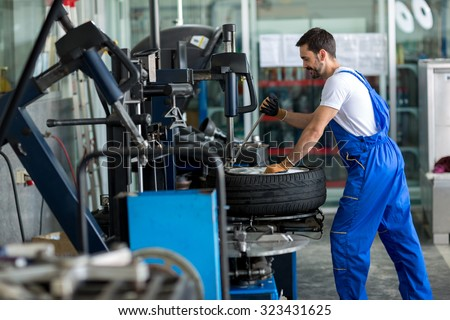 repairman balancing  car wheel on balancer in workshop - stock photo