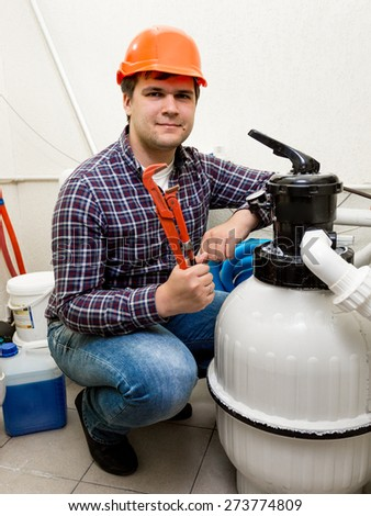 Repairman engineer posing at high pressure circulating system with red pliers - stock photo