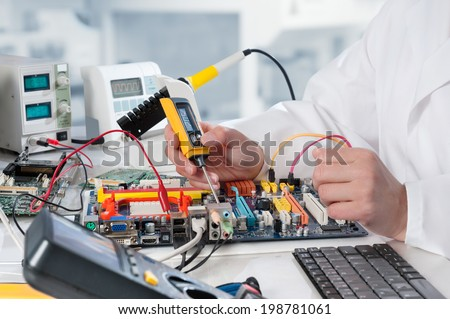Repairman fixes electronic equipment in service center - stock photo