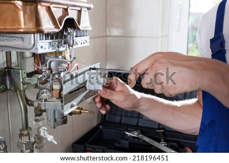 Repairman fixing a gas water heater with a screwdriver - stock photo