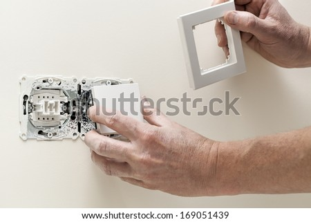 Repairman hands putting a cover to light switch - stock photo