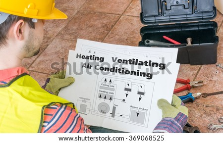 Repairman is looking at documentation of HVAC (Heating, Ventilating, Air Conditioning). - stock photo