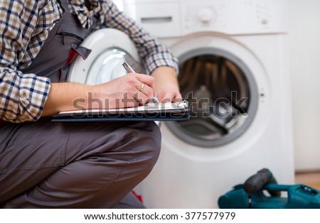 Repairman is repairing a washing machine on the white background. Entering malfunction - stock photo