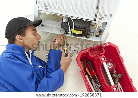 Repairman makes refrigerator appliance maintenance works  - stock photo