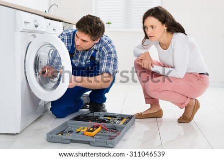 Repairman Repairing Washer In Front Of Young Woman In Kitchen At Home - stock photo