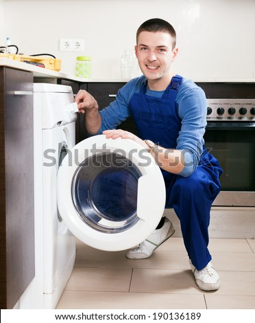 Repairman repairing washing machine at kitchen - stock photo