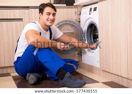 Repairman repairing washing machine at kitchen