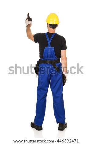 Repairman wearing hard hat pointing up - stock photo