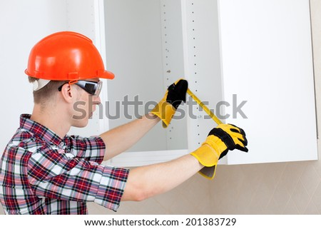 repairman with a tape measure and a red protective helmet