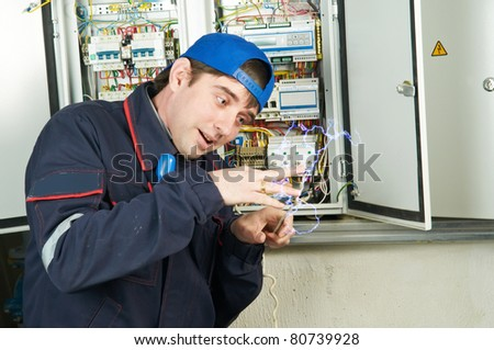 Repairman worker electrician in uniform under high voltage electric shock accident - stock photo