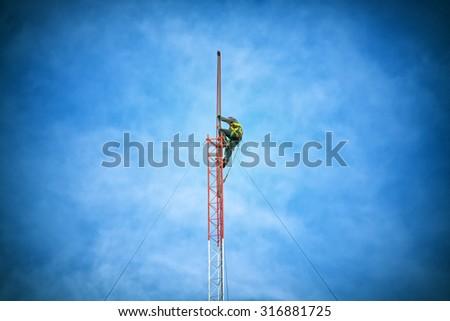 Repairman working on communications tower - stock photo