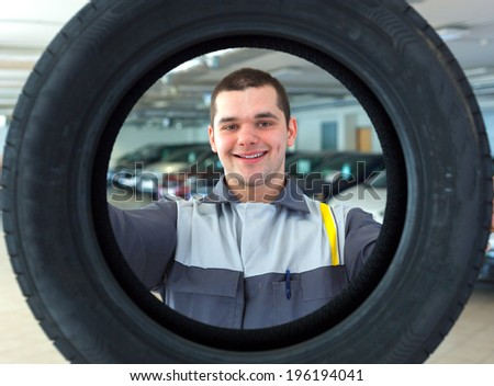 Repairmen automobile mechanic with car tire - stock photo