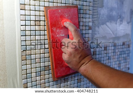 Repairs in the apartment: installing the mosaic tile on the wall. / A worker are pressing down the mosaic using a Rubber Grout Float. - stock photo