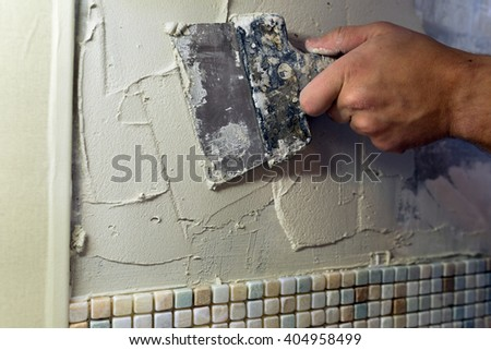 Repairs in the apartment: spreading of tile adhesive with a trowel. / Install mosaic tiles. - stock photo