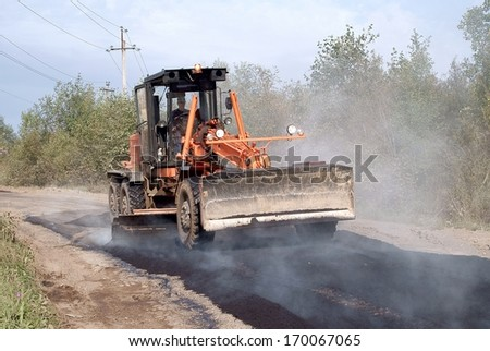Repairs of the road. Leveling the asphalt mixture grader - stock photo
