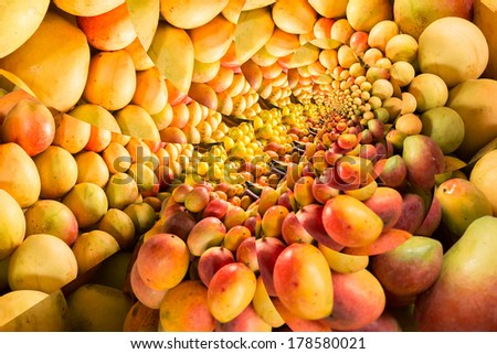 Repeating pattern of a pile of ripe mangos on a fruit stand - stock photo