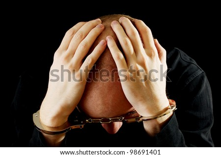 Repentant bandit in handcuffs isolated on black - stock photo