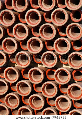 Repetitive stack of clay pipes on construction site - stock photo