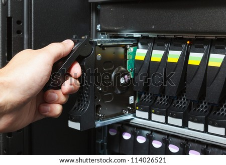 replacing a failed hard drive in the storage system in the data center - stock photo