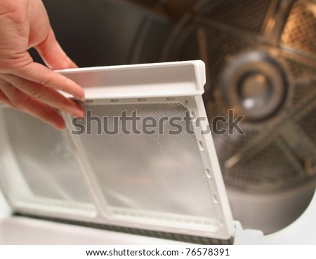 replacing the screen in the lint trap of a clothes dryer - stock photo
