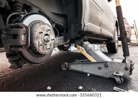 Replacing wheels on a car, jack holds the auto body in the raised position - stock photo