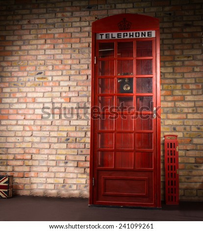 Replica iconic British telephone booth standing against a brick wall with a telephone sign and crown on the front - stock photo