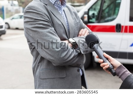 Reporter holding a microphone, making a live broadcast. - stock photo