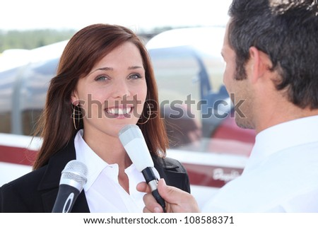 Reporter interviewing woman in airport - stock photo