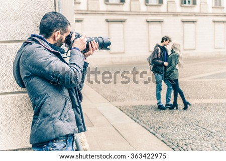 Reporter photographing a famous vip couple on a romantic date - Detective inquiring in a couple betrayal - stock photo