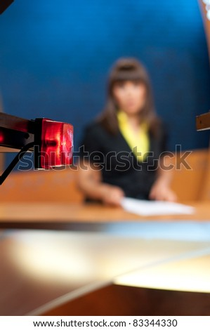 Reporter presenting news in TV studio - On the air sign. Focus on AIR sign - stock photo