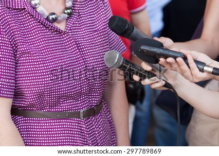 Reporters taking interview at news conference - stock photo