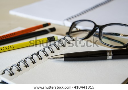 Representative pen laying on a blank note book with pencils and glasses  on table. Tilt-up  close-up view