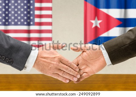Representatives of the USA and Cuba shake hands - stock photo