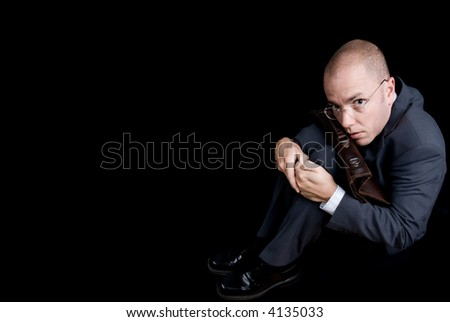Repressed businessman is sitting in a dark room.Use it for business concepts - stock photo