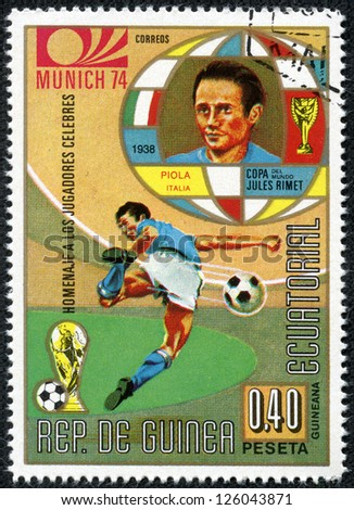 REPUBLIC OF EQUATORIAL GUINEA - CIRCA 1974: A stamp printed in the Republic of Equatorial Guinea shows football player (Champions Cup : Munich, Germany) and portrait piola(Italy), circa 1974. - stock photo