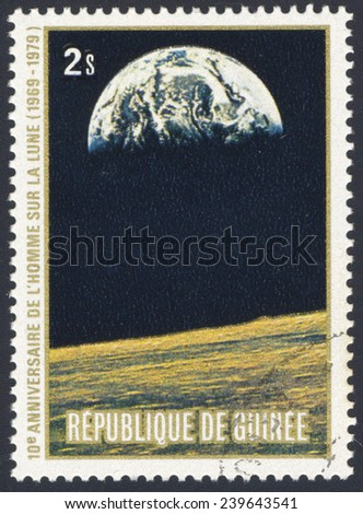REPUBLIC OF GUINEA - CIRCA 1979: A stamp printed in the Republic of Guinea shows the Apollo 11 Moon Landing and first step on The Moon surface - view of Earth, circa 1979 - stock photo