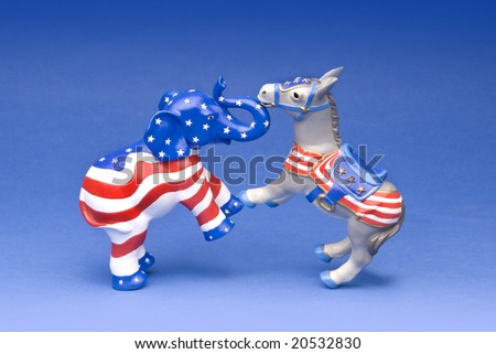 Republican and Democratic party mascots fighting it out on a blue background - stock photo