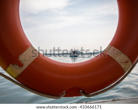 Rescue boat in the sea that look through orange ring buoy - stock photo