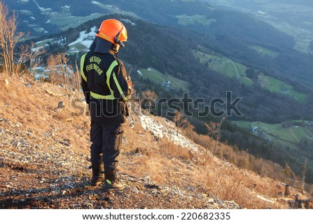 Rescue Fire worker in the Austrian  Mountain helping a paraglider  - stock photo