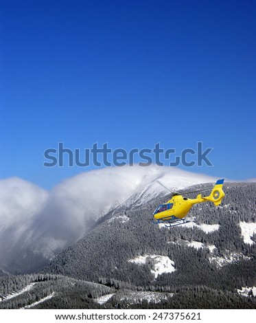 Rescue helicopter in the mountains - stock photo