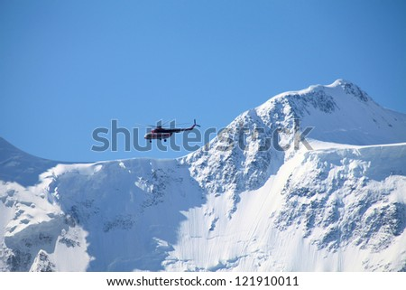 Rescue helicopter over a Belukha peak, Altai, Russia