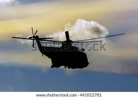 rescue helicopter silhouette in atlantic ocean at sunset