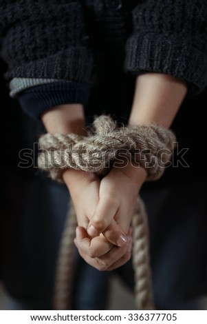Rescue me. Poor depressed little girl having her hands tied and folding her hands  - stock photo