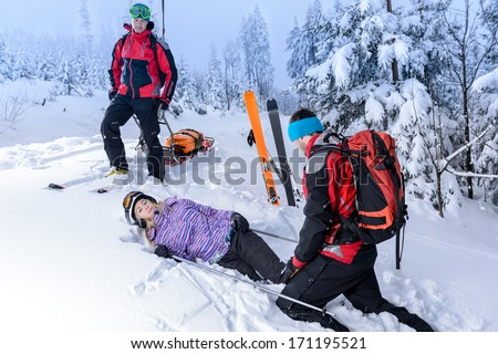 Rescue ski patrol help injured woman skier lying in snow - stock photo