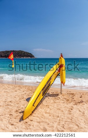 Rescue surfboard on the beach on summer day. Blue sky and sea in the background - stock photo