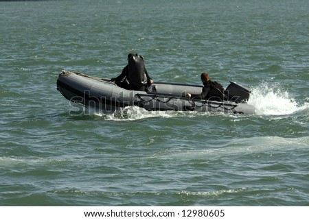 Rescue team in action on a inflatable boat. - stock photo