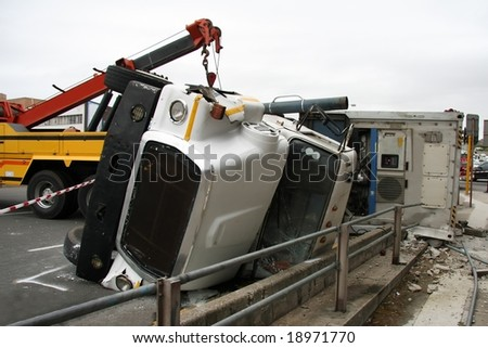 Rescue truck and overturned truck against pedestrian railings - stock photo